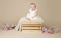 Baby girl with cherry blossom flowers in spring dress on blanke beautiful sitting a knit white blanket a wood crate Stock Image