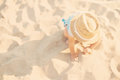 Baby girl child with straw hat and blue dress playing with sand at the beach in summer. Little girl sitting on the shore of the se Royalty Free Stock Photo