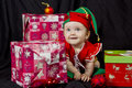 Baby girl christmas elf on black a dressed up as a little in a cute outfit sitting in front of a background wearing a colourful Stock Photos