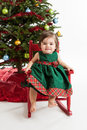 Baby girl at christmas tree one year old sitting in front of the Royalty Free Stock Images