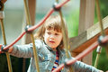 Baby girl climbing at ropes on playground
