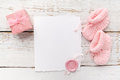 Baby girl clothes, blank card with wax seal and small present box on white wooden background. Flat lay. Owerhad view Royalty Free Stock Photo