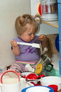 Baby girl with cooking pans Royalty Free Stock Photos