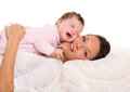 Baby girl crying and mother lying together on white fur Stock Photo