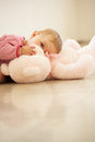 Baby Girl Cuddling Pink Teddy Bear At Home Stock Photography