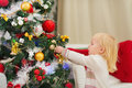 Baby girl decorating Christmas tree Stock Photo