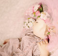 Baby girl dreaming in flowers and lace on pink background Royalty Free Stock Photography
