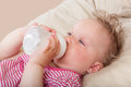 Baby girl drinking milk cute lying in bed and from bottle Royalty Free Stock Photography