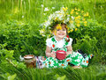 Baby girl is drinking milk sitting on a glade foto Stock Image