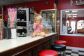 Baby girl eating candy at ice cream shoppe a month old is sitting on the sale counter an old fashion hard Royalty Free Stock Photos