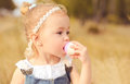 Baby girl eating cupcake outdoors closeup portrait of caute cake Stock Photo