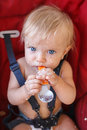 Baby girl eating on her own with spoon Royalty Free Stock Photo