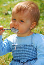 Baby girl eating by herself outdoor Royalty Free Stock Image
