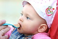 Baby girl eating from spoon Royalty Free Stock Photo