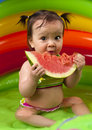 Baby girl in eating watermelon wading pool Stock Images