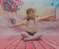 Baby girl in a flight helmet on the background of the balloon is flying Royalty Free Stock Photo