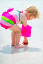 Baby girl found shell on sea shore rear view in swimsuit Royalty Free Stock Photo