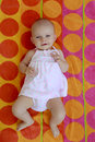Baby girl of four months laying on the beach towel of red and or orange circles Royalty Free Stock Image