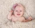 A baby girl on fur lying looking at the camera and smiling Stock Photo