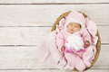 Baby girl with gift sleeping on wooden background, newborn in ba Royalty Free Stock Photo