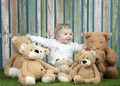 Baby girl with group of teddy bears seated on grass in front a fence Stock Image