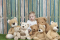 Baby girl with group of teddy bears seated on grass in front a fence Stock Photo