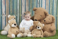 Baby girl with group of teddy bears seated on grass in front a fence Royalty Free Stock Photo