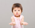 Baby girl with hand gesture showing nothing gray background Stock Photo