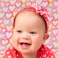 Baby girl with headband an adorable wearing a red a decorative flower lying on a blanket hearts design printed on it Stock Image