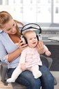 Baby girl with headphones sitting on mother s lap listening to music through both smiling Stock Photography