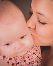 A baby girl and her mother being kissed by Stock Images
