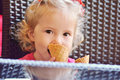 Baby girl with ice cream sitting in cafe Stock Image