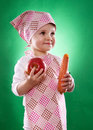 The baby girl with a kerchief and kitchen apron holding an vegetable isolated on green background Royalty Free Stock Image