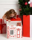 Baby Girl Kid playing with christmas red house in play room at home or kindergarten with little dolls toys Royalty Free Stock Photo