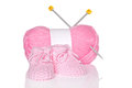 Baby girl knitted booties with pink wool and knitting needles isolated on a white background Stock Image