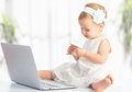 Baby girl with laptop and credit card shopping on internet the Stock Photos