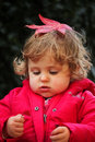 Baby girl with a leaf big red on her head autumn Stock Image