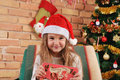 Baby girl with little red box in hands on the chair near Christmas tree