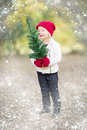 Baby Girl In Mittens Holding Small Christmas Tree with Snow Effe Royalty Free Stock Photo
