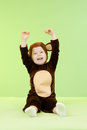 Baby girl in monkey costume over green background Royalty Free Stock Images