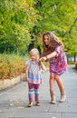 Baby girl and mother in city park pointing on something while walking Royalty Free Stock Photo