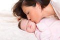 Baby girl and mother kissing her lying happy on white Stock Images