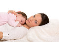 Baby girl and mother lying happy together on white fur Stock Image