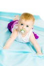Baby girl with pacifier crawling on the blue coverlet eyed Stock Photo