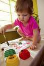 Baby girl with paint brush Stock Image