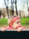 Baby girl in park holding on a bench with space for text Royalty Free Stock Photo