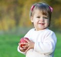Baby girl in the park holding red apple young Stock Photography