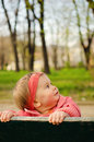 Baby girl in park looking up Stock Photography