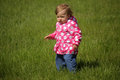 Baby girl in the park on a windy day standing grass garden spring Royalty Free Stock Photos