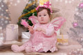 Baby girl with pink butterfly wings sitting under Christmas tree Royalty Free Stock Photo